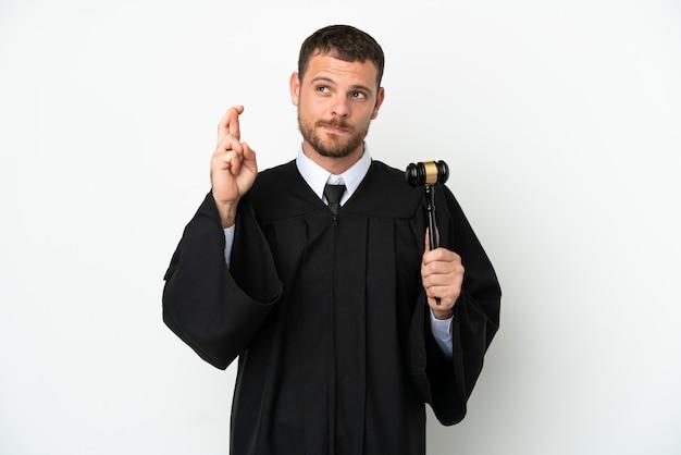 Juez hombre caucásico aislado sobre fondo blanco con los dedos cruzando y deseando lo mejor
