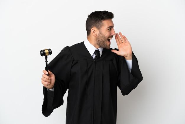 Juez hombre caucásico aislado sobre fondo blanco gritando con la boca abierta hacia un lado