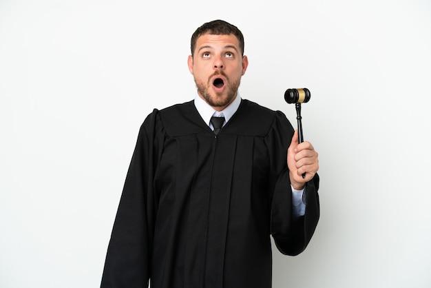 Juez hombre caucásico aislado sobre fondo blanco mirando hacia arriba y con expresión de sorpresa
