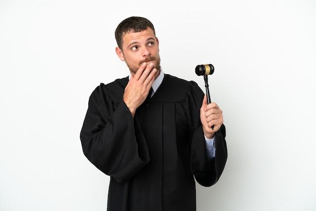 Juez hombre caucásico aislado sobre fondo blanco mirando hacia arriba mientras sonríe