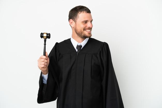 Juez hombre caucásico aislado sobre fondo blanco mirando de lado