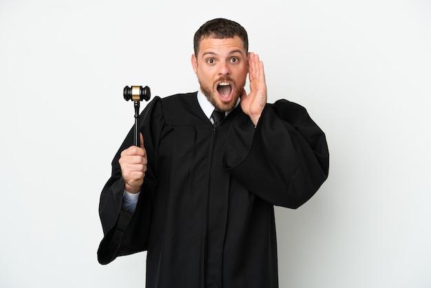 Juez hombre caucásico aislado sobre fondo blanco con sorpresa y expresión facial conmocionada