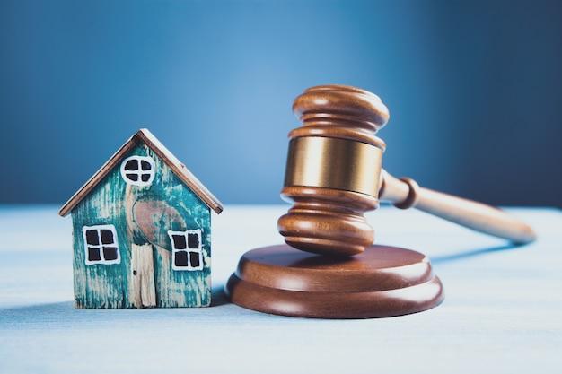 Juez martillo y casas sobre un fondo de madera. el concepto de subasta de bienes raíces o división de una casa en caso de divorcio.
