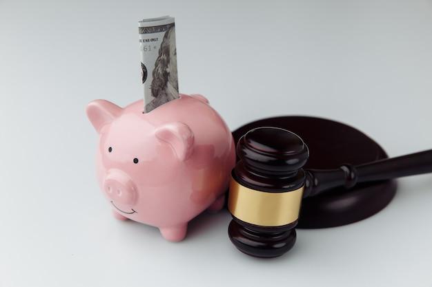 Juez martillo y hucha rosa con billete de un dólar en un escritorio blanco