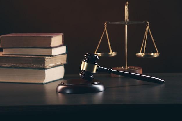 Juez martillo y libro con abogados de justicia con reunión de equipo en bufete de abogados en segundo plano.