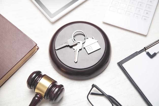 Juez martillo, modelo de casa, llaves, libro, portapapeles, calculadora, tableta. vista superior