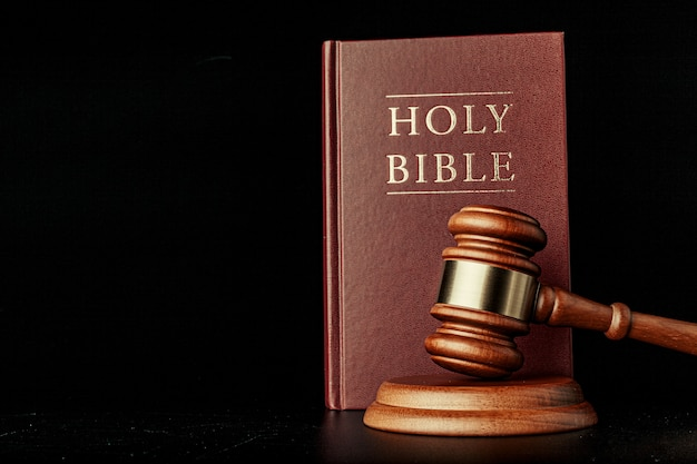 Juez martillo con la sagrada biblia sobre fondo negro