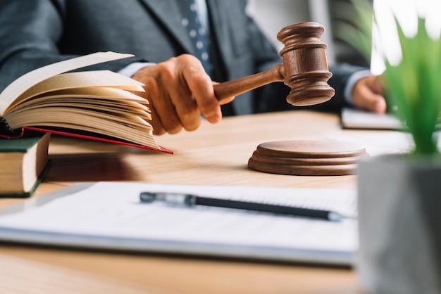 Juez masculino que da veredicto golpeando el mazo en el escritorio