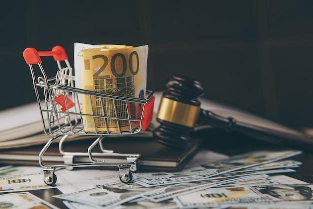 Juez o martillo de la subasta y la cesta de billetes en euros sobre fondo negro