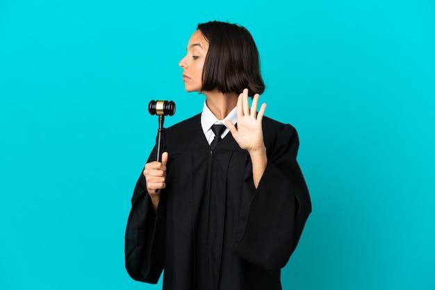Juez sobre fondo azul aislado haciendo gesto de parada y decepcionado