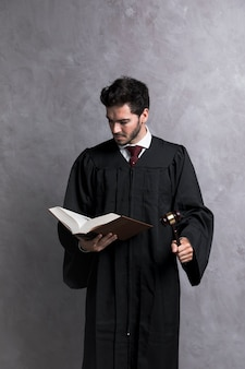 Juez de vista frontal con libro de lectura de martillo