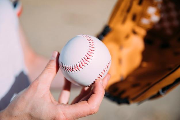 Jugador adolescente con béisbol y guante.