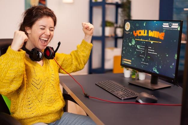 El jugador alegre celebra el videojuego en línea del tirador espacial ganador de la victoria en una poderosa computadora personal