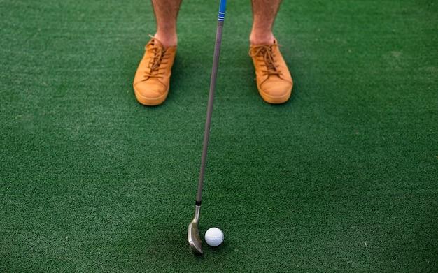 Jugador de alto ángulo golpeando la pelota de golf