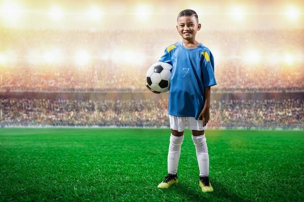El jugador asiático de los niños del fútbol en el jersey azul que se coloca y presenta a la cámara en el estadio