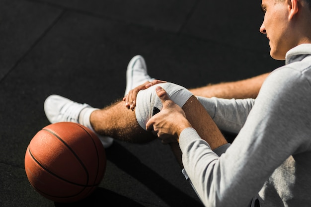 Jugador de baloncesto aplicando vendaje en la rodilla