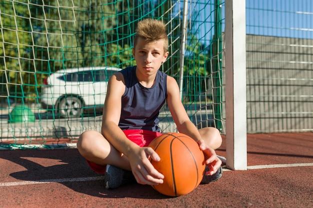 Jugador de baloncesto callejero de chico adolescente en la cancha de baloncesto de la ciudad