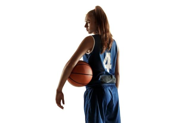 Jugador de baloncesto femenino caucásico joven del equipo que presenta confiado con el balón aislado en el fondo blanco.