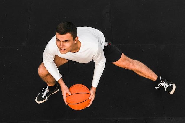 Jugador de baloncesto guapo estirando tiro completo