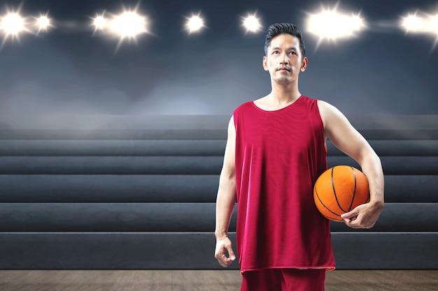 Jugador de baloncesto hombre asiático sosteniendo la pelota en su mano
