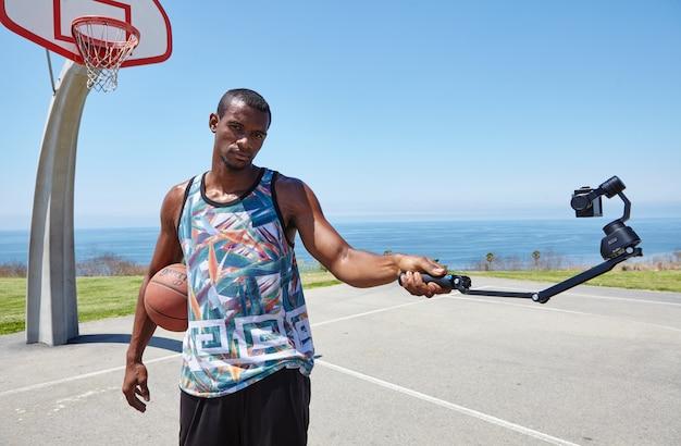 Jugador de baloncesto junto al mar con cámara selfie