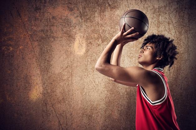 Jugador de baloncesto lanza la pelota sobre fondo marrón grunge