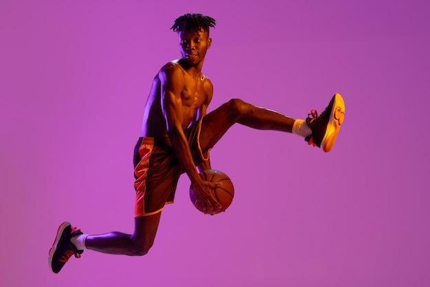 Jugador de baloncesto masculino afroamericano en movimiento y acción aislado en púrpura