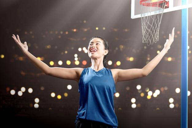 Jugador de baloncesto de mujer asiática con una expresión feliz