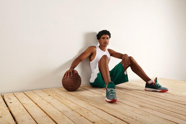 Jugador de baloncesto negro cansado y pensativo en outift de baloncesto verde y blanco sentado en el piso de madera clara apoyando su mano en una pelota de baloncesto marrón grunge