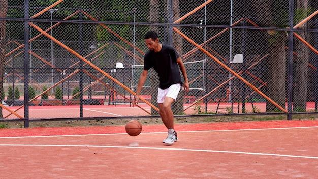 Jugador de baloncesto negro jugando en el campo