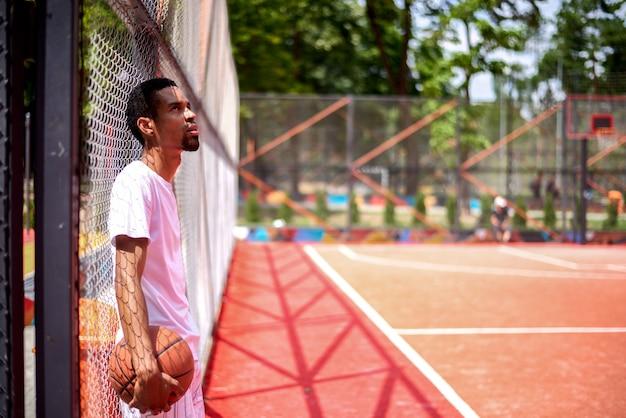 Jugador de baloncesto negro posando en el campo al aire libre