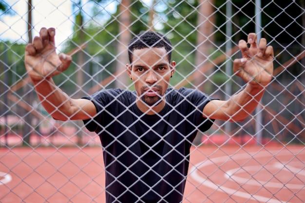 Jugador de baloncesto negro sosteniendo la valla de alambre con las manos