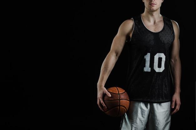 Jugador de baloncesto posando con pelota sobre fondo negro