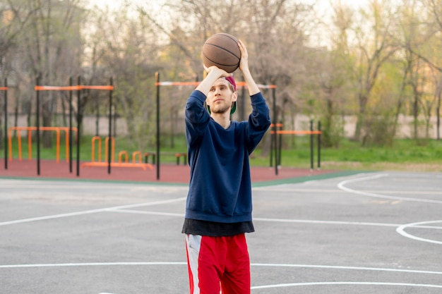 Jugador de baloncesto practicando ejercicios de tiro al aire libre en las canchas de la calle de la ciudad