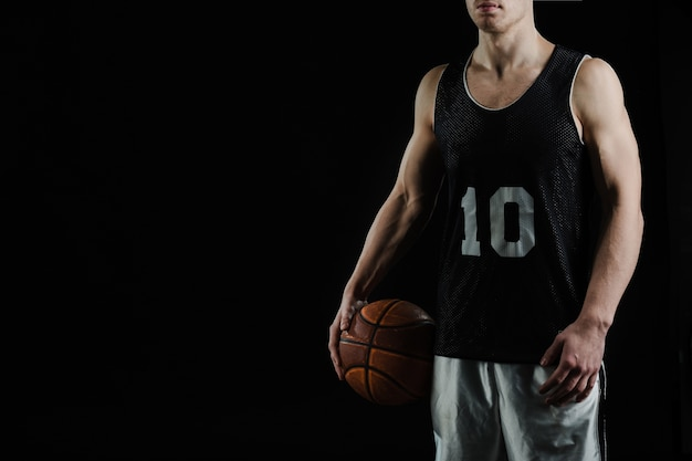 Jugador de baloncesto profesional sujetando la pelota debajo del brazo