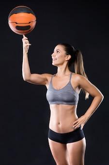 Jugador de básquet hermoso que hace girar la bola en su dedo sobre fondo negro.
