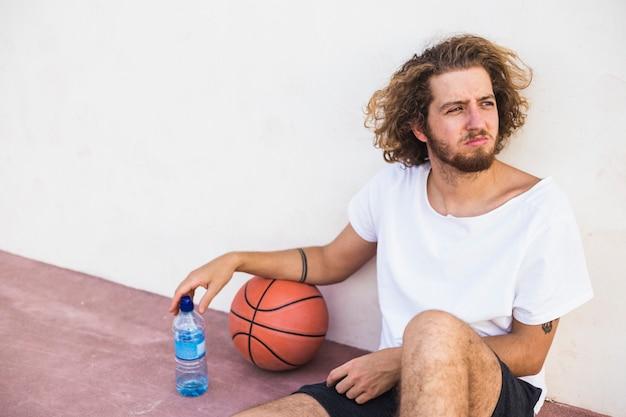 Jugador de básquet joven relajado que se sienta con la bola y la botella de agua