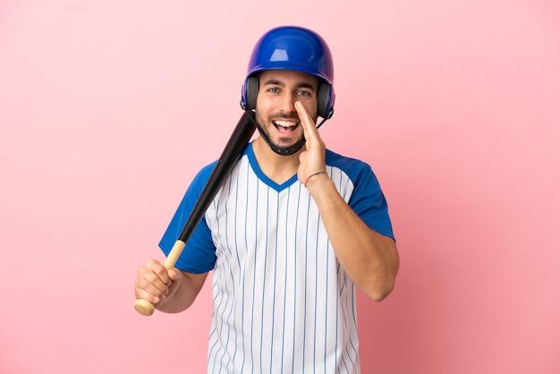 Jugador de béisbol con casco y bate aislado sobre fondo rosa gritando con la boca abierta