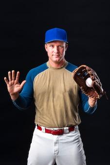 Jugador de béisbol con gorra posando con guante