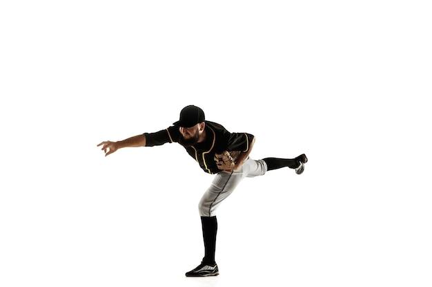 Jugador de béisbol, lanzador con uniforme negro practicando y entrenando aislado en una pared blanca. joven deportista profesional en acción y movimiento. estilo de vida saludable, deporte, concepto de movimiento.