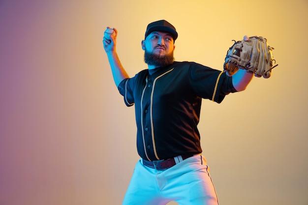 Jugador de béisbol, lanzador con uniforme negro practicando y entrenando sobre fondo degradado con luz de neón.
