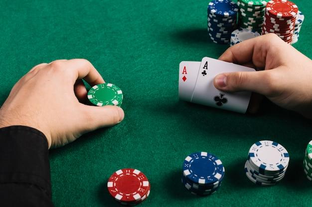 Jugador con dos ases y fichas jugando al poker.