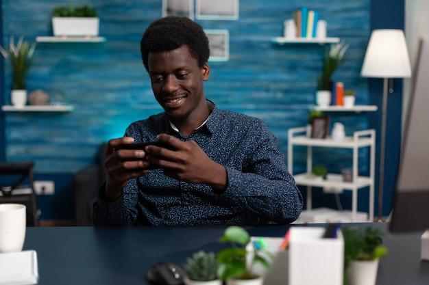 Jugador estudiante sosteniendo smartphone en posición horizontal