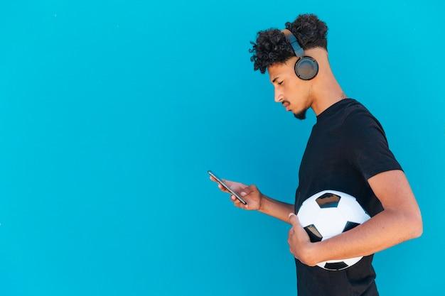 Jugador étnico con fútbol usando teléfono y auriculares.