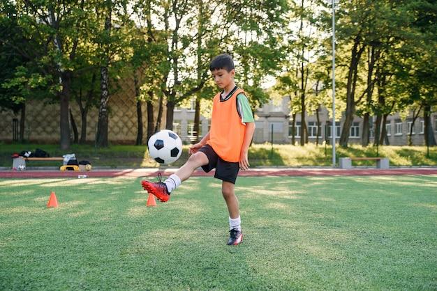 Jugador de fútbol adolescente motivado rellena el balón de fútbol en la pierna. practicando ejercicios deportivos en artificial