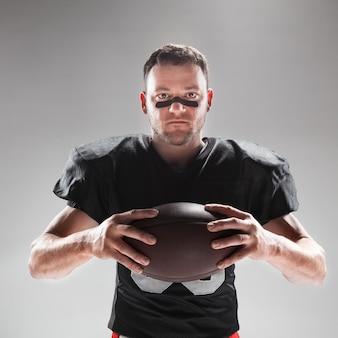 Jugador de fútbol americano posando con balón