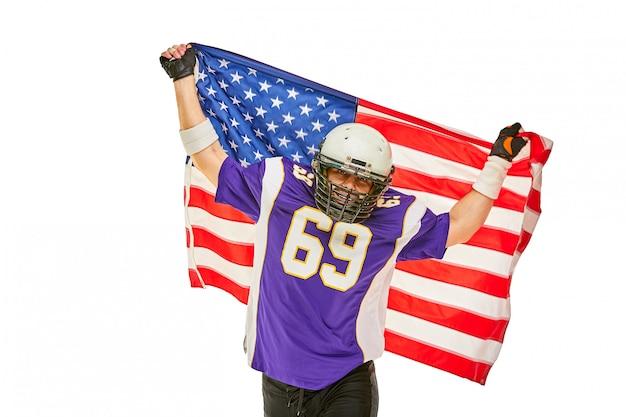 Jugador de fútbol americano con uniforme y bandera estadounidense orgulloso de su país, en un espacio en blanco.