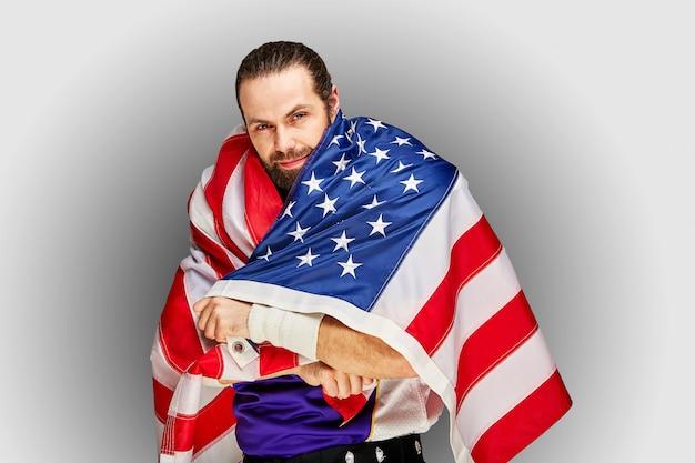 Jugador de fútbol americano con uniforme y bandera estadounidense orgulloso de su país, en una pared blanca