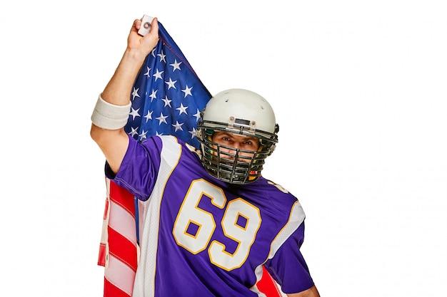 Jugador de fútbol americano con uniforme y bandera estadounidense orgulloso de su país, sobre un fondo blanco.