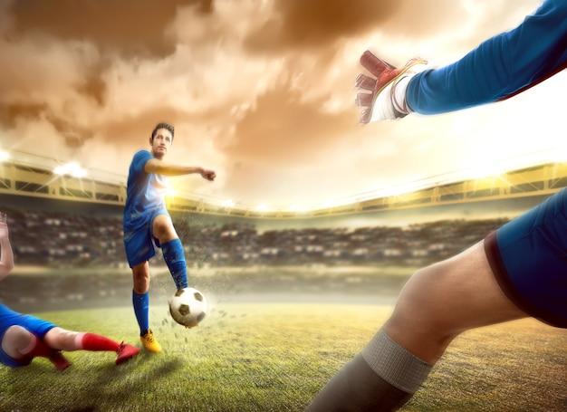 Jugador de fútbol asiático hombre deslizándose frente a la pelota de su oponente antes de patear la pelota a la portería